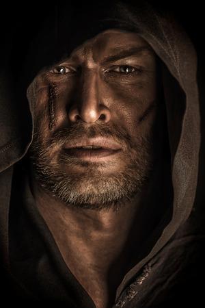 Retrato de un guerrero valiente trotamundos en un manto negro. Fantasía histórica. Víspera de Todos los Santos.