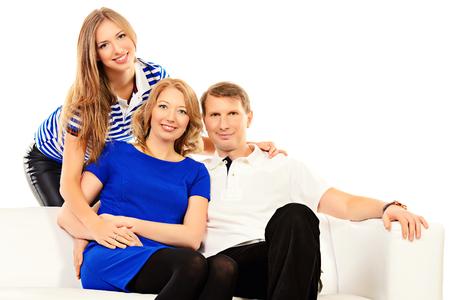 幸せな高齢者の親は彼らの大人の娘とソファの上に座って。白で隔離されました。