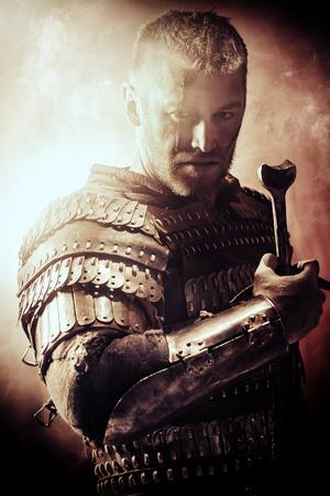 Portret van een moedige oude krijger in harnas met zwaard. Stockfoto