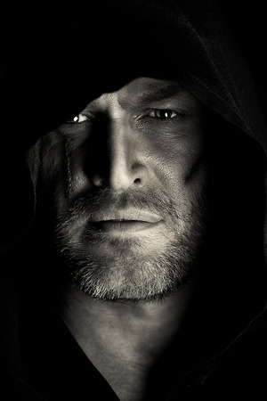 Portrait of a courageous warrior wanderer in a black cloak. Historical fantasy. Halloween. Black-and-white photo. Imagens