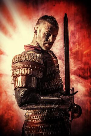 Portret van een moedige oude krijger in harnas met zwaard.