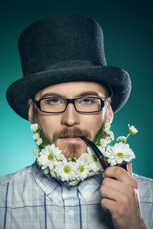 Extravagant man with a beard of flowers wearing elegant top hat and smoking a pipe.