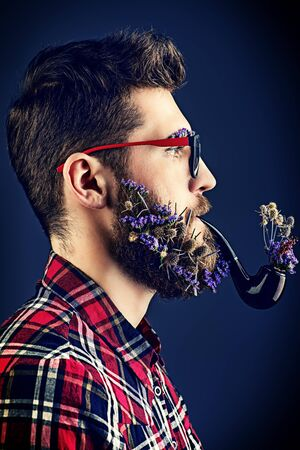 Handsome young man in glasses and a beard of flowers smoking a pipe. Profile portrait. Foto de archivo