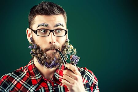Extravagant young man in glasses and a beard of flowers smoking a pipe.