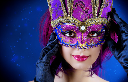 Beautiful young woman in carnival mask. Masquerade. Dark background.