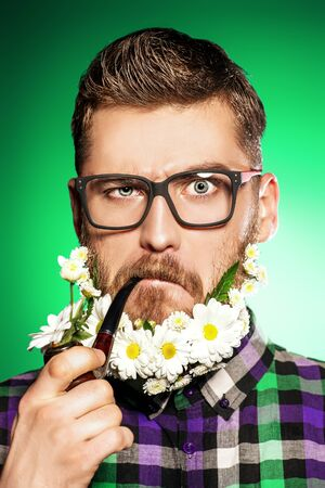 Handsome young man in glasses and a beard of flowers smoking a pipe.