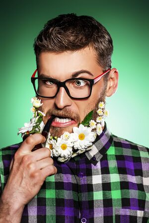 Funny young man in glasses and a beard of flowers smoking a pipe.  Foto de archivo