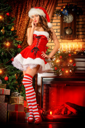 Sexual young woman in Santa Claus costume posing in Christmas decorations.