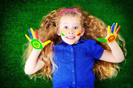 pintura en la cara: Niña de risa pintada en colores brillantes tumbado en la hierba verde. Infancia feliz.