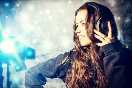 Beautiful expressive girl listening to music in headphones. Disco, party. photo