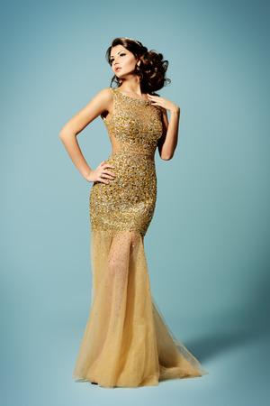 見事なドレスを着た女性豪華な金色のファッション撮影。完全な長さの肖像画。