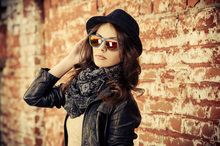 Beautiful young woman in black leather jacket posing over brick wall. Stock Photo