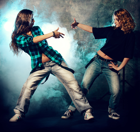 urban dance: Modern hip-hop dancers over grunge background. Urban, disco style.