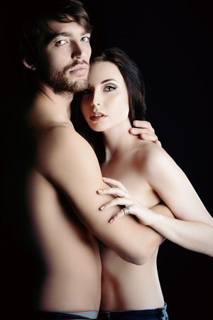 Beautiful passionate naked couple in love. Over black background. photo