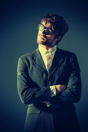 Portrait of a handsome man in elegant black suit and spectacles. Over dark background. photo