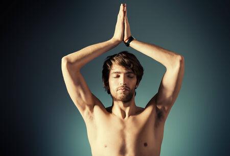 Handsome young man doing yoga exercises. Meditation. Studio shot. photo