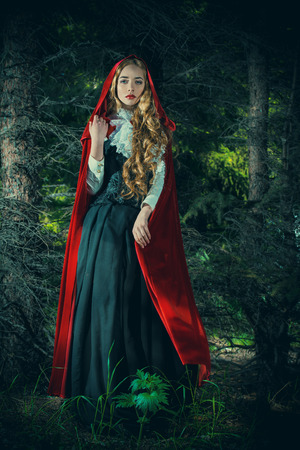 mysterious: Beautiful blonde woman in  old-fashioned dress and red cloak in a fairy forest.