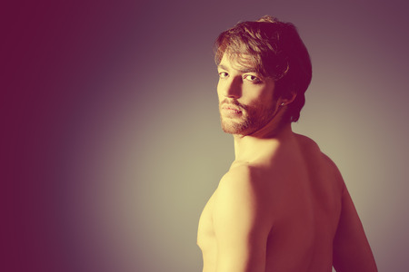 Handsome shirtless young man posing at studio.  photo