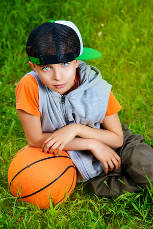 Cool boy lying on a grass with a basketball at a park. Summer day.  photo