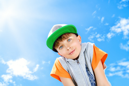 Cheerful smiling boy looking at the camera against the blue sky. Summer.  photo
