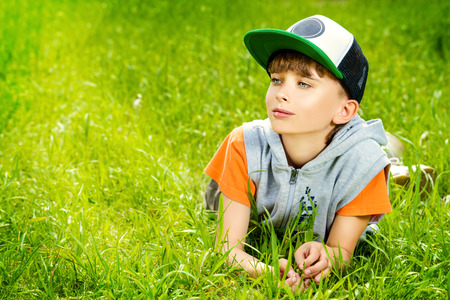 Smiling boy lying on a grass at a park. Summer day.  photo