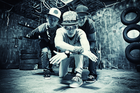 Group of cool guys hang out in the garage. Hip-hop style.  photo