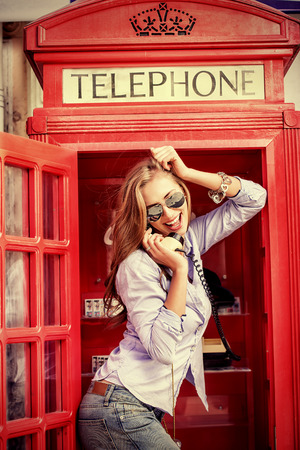 Pretty young woman talking on the phone in telephone booth. Europe, England. Vacation, tourist trip. photo