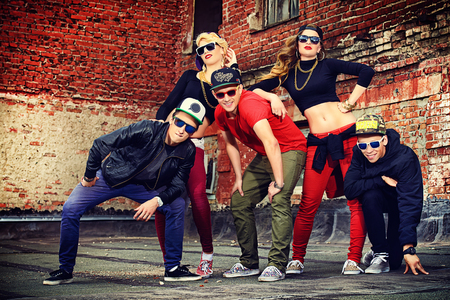 hip hop style: Group of young modern people posing together with fun. Urban lifestyle. Hip-hop generation.