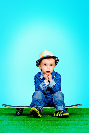 Portrait of a cute little boy in jeans clothes sitting on a skateboard photo
