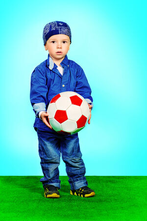 freetime activity: Adorable little boy in jeans clothes standing on a grass with a ball