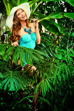 Beautiful young woman in swimsuit stands among the tropical plants photo