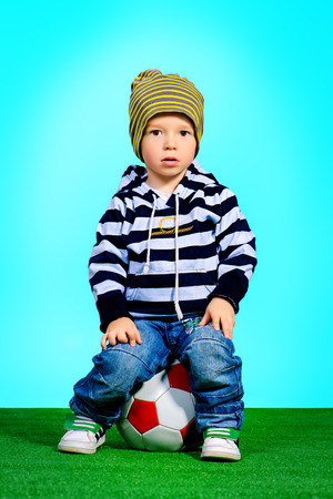 Adorable little boy in jeans clothes with football photo