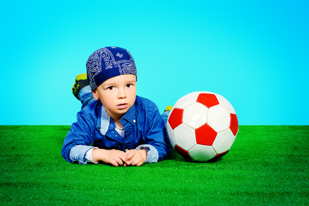 Adorable little boy in jeans clothes lying on a grass with a ball photo
