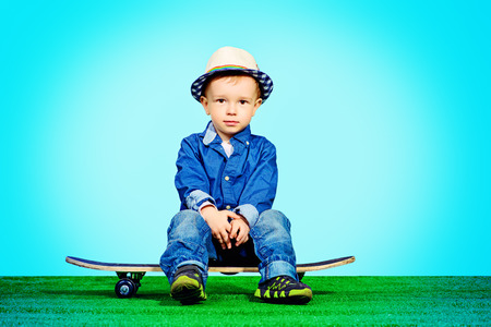 freetime activity: Portrait of a cute little boy in jeans clothes sitting on a skateboard