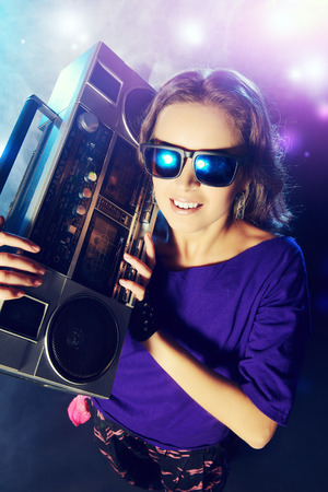 urban dance: Portrait of a modern girl with tape recorder over grunge background Stock Photo