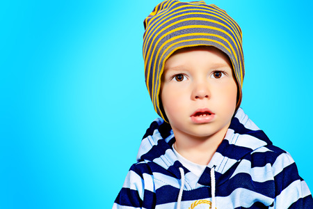 Portrait of a cute 2 years old boy over blue background photo
