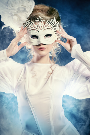 Portrait of a beautiful fashion model in elegant white dress and a mask. Carnival, masquerade. photo