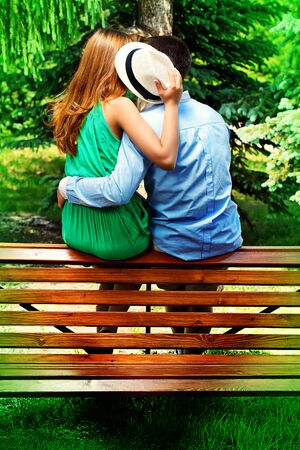young people tenderly kissing on a park bench love concept stock