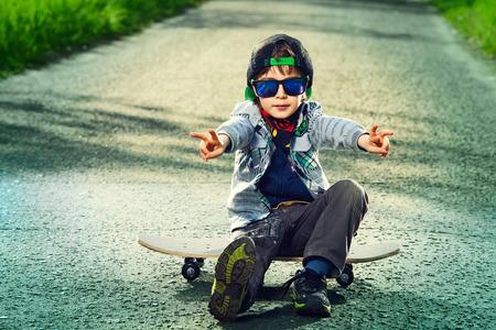 Cool 7-jarige jongen met zijn skateboard op de straat. Kindertijd. Summertime.