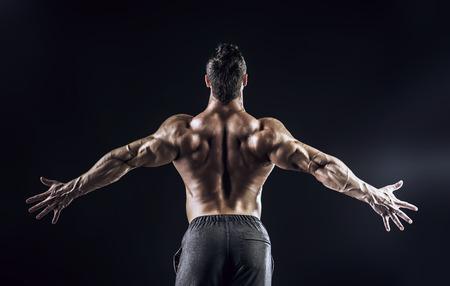 Mooie gespierde bodybuilder van een man die terug op een donkere achtergrond staat.