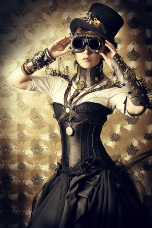 Portrait of a beautiful steampunk woman over vintage background. Фото со стока