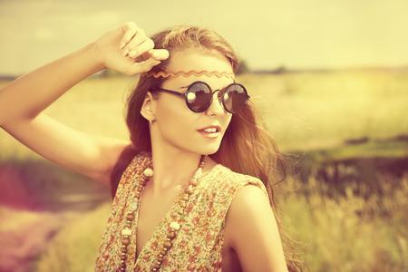 ロマンチックなヒッピーの女の子のフィールドに立っています。夏。ヒッピー スタイル。
