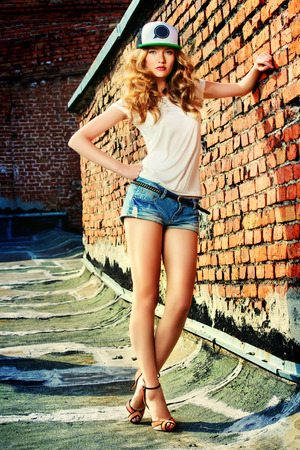 Beautiful modern girl near the brickwall. Youth style. Fashion shot. Фото со стока