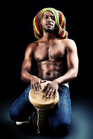 Rastafarian african american man playing his drum. Over dark background.