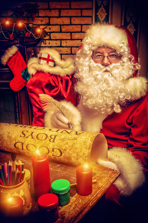 Santa Claus writing a list of good boys and girls at home. Christmas.