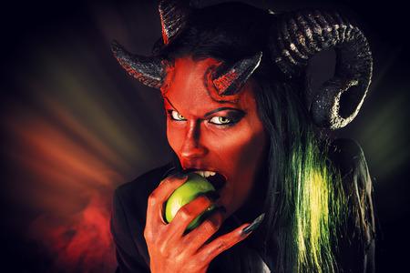 Portret van een duivel met hoorns die appel. Duivelse verleiding. Fantasie. Kunstproject.