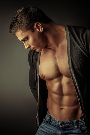 Portret van een sexy gespierde jonge man die zich voordeed op donkere achtergrond.