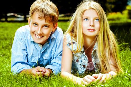 Twee vrolijke tieners op het gras in het park. Zomer. Vriendschap.
