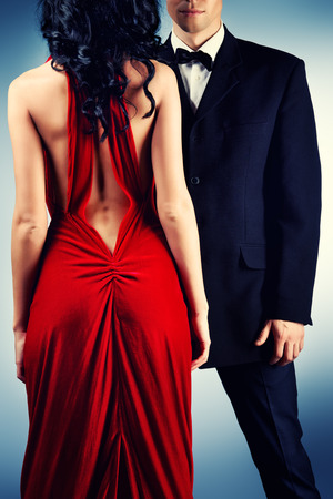 Mooie jonge paar in liefde in avondjurken die bij studio stellen. Fashion.