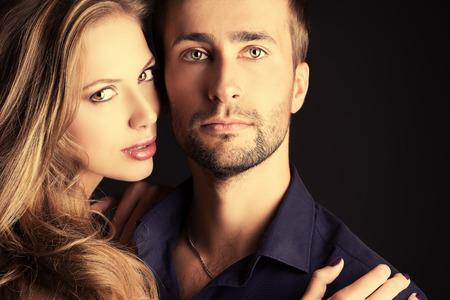 暗い背景上のスタジオでポーズ恋に美しい若いカップルの肖像画。